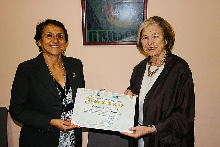 Ursula Männle hält zusammen mit Miriam Redón Fernández eine Urkunde.