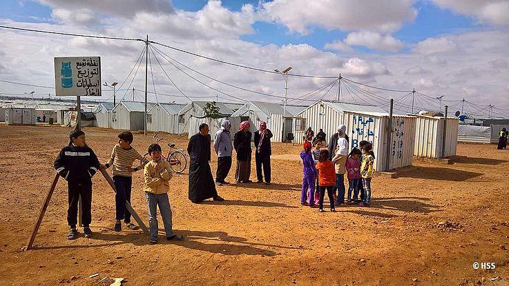 Kinder und Jugendliche am Rand des staubigen Lagers mitten in der Wüste