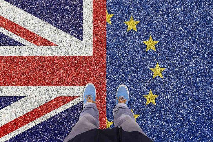 Britische und Europaflagge. Zwei Füße. Einer steht auf der britischen, einer auf der Europaflagge.