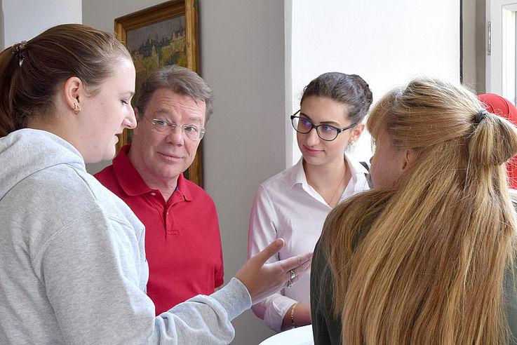 Gruppe junger Menschen diskutiert miteinander und mit Trainer Groß