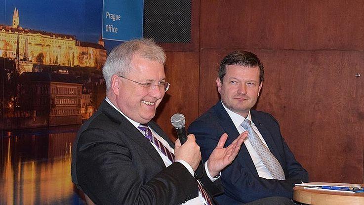 Ferber (links) und Kastler auf dem Podium. Ferber spricht gerade lachend ins Mikrofon. Kastler blickt ihn an.