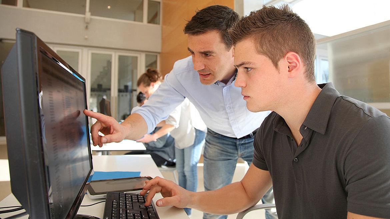 Lehrer steht neben dem Schüler, der am Computer sitzt, zeigt auf den Monitor