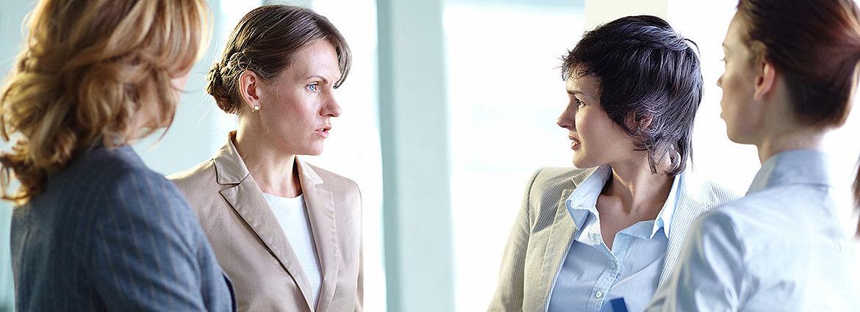 Vier Frauen stehen in im Büro beieinander und sprechen miteinander