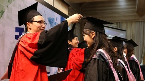 Chinesische Studenten bei der Zeugnisübergabe mit schwarzen eckigen Hüten mit Bommel.