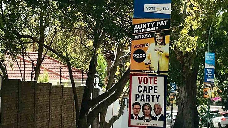Laternenmast, an dem übereinander 5 Wahlplakate angebracht worden sind.