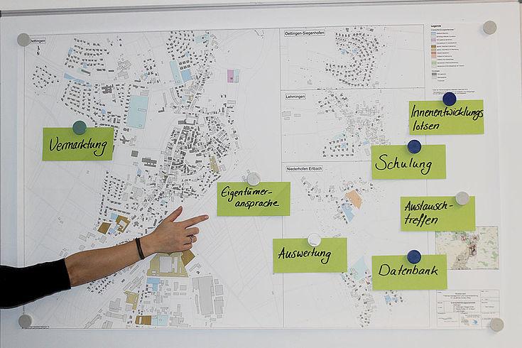 """An einer Wand heftet ein Karte eines Gemeindegebiets, auf der Postets mit Aufschriften wie Schulung, Eigentümeransprache etc. heften. Eine Hand zeigt auf ein Postet mit der Aufschrift """"Eigentümer ansprechen."""