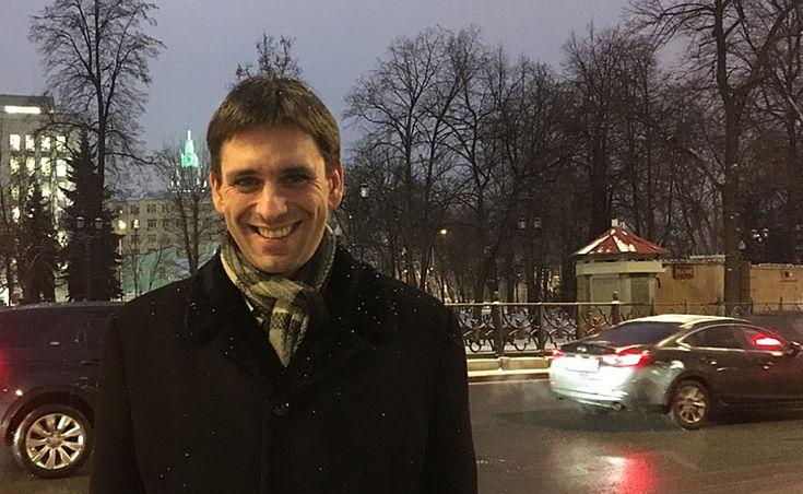 Ein lächelnder Mann Anfang 40 vor einer viel befahrenen Moskauer Straße im Abendlicht, dunkler Mantel, Schal. Es schneit leicht.
