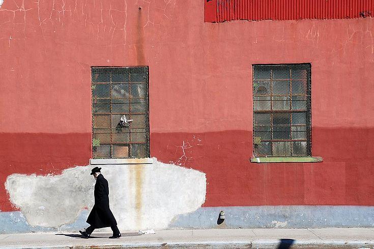 Orthodoxer Jude geht an einer Hauswand entlang. Kopf hängt herunter.