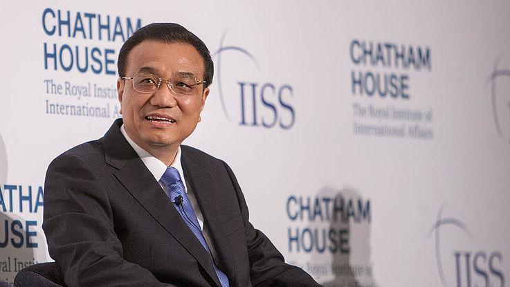 Chinesischer Premierminister vor einer Stellwand von Chatam House, sitzend. Lächelt.