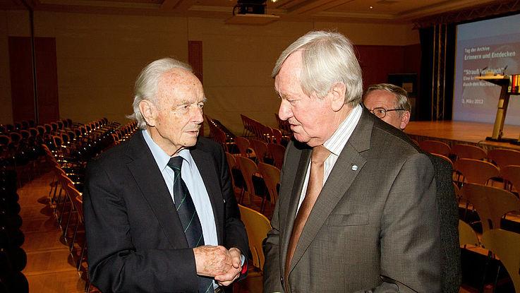 Otto Meitinger links neben Zehetmair zuhörend. Schmal, etwas ausgezehrt, sich zurückziehendes, schütteres weißes Haar, dunkler Anzug. Zehetmair robuster, volleres weißes Haar und markante Nase, brauner Anzug.