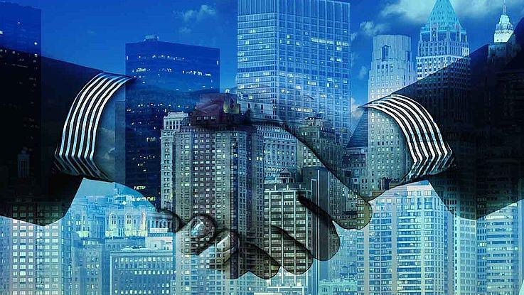 Zwei transparente Hände beim Hand-Shake vor dem Hintergrund der New Yorker Skyline in Blau gehalten.