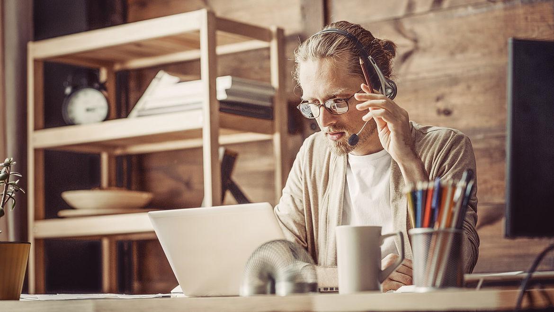 Lehrer unterrichtet von Zuhause aus mit Headset und Laptop.
