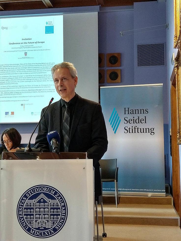 Ein Mann steht an einem Podium und spricht gerade. Dahinter eine Leinwand und ein Roll-Up der Hanns-Seidel-Stiftung.