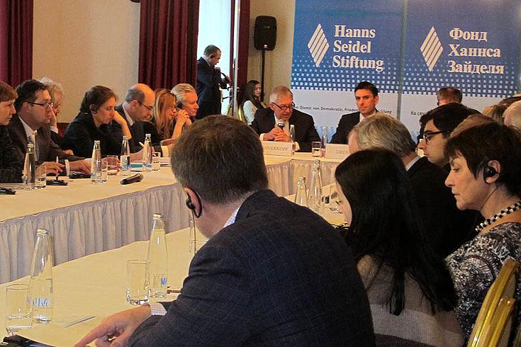 Konferenztisch mit diskutierenden Delegierten