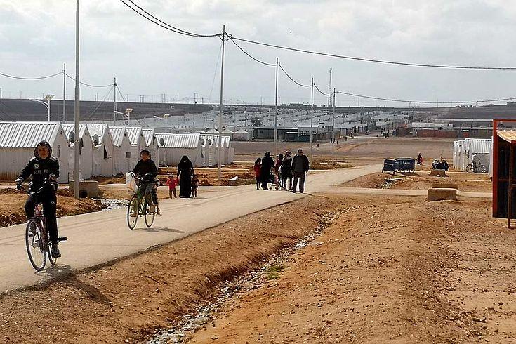 Geteerte Staße am Rand des Lagers. Jugendliche auf Fahrrädern