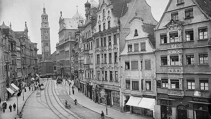 Eine alte Aufnahme der Maximiliansstraße mit den Trambahnschienen in der Mitte und Passanten