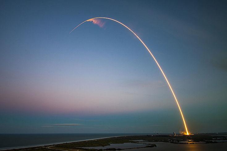Raketenstart an einer Küste. Im Bild sieht man die Spur, die der Antrieb in einer schrägen Kurve durch den abendlichen Himmel zieht.
