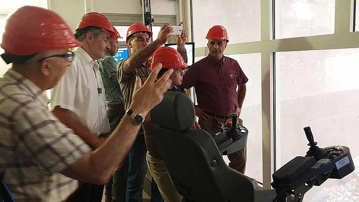 Sechs Männer mit roten Helmen stehen in einem Raum vor einem großen Fenster und sehen sich ein technisches Gerät an.