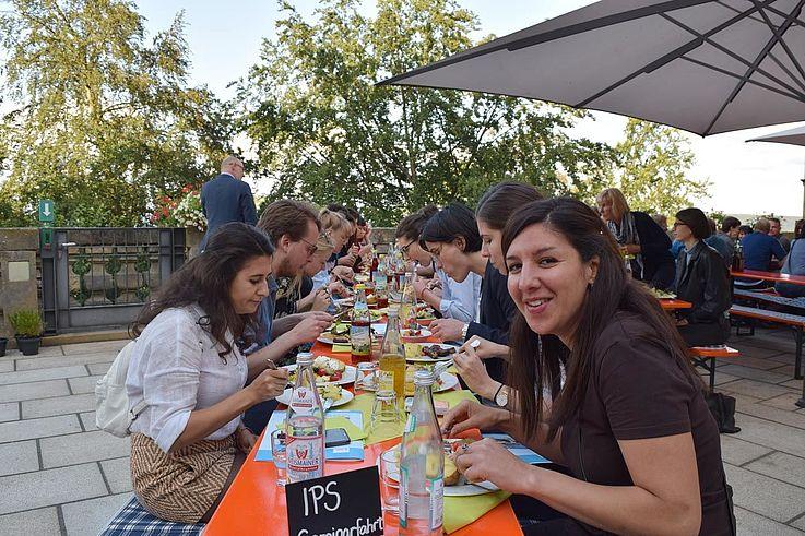 Junge Menschen auf einer gepflasterten Terrasse beim Essen an einem langen Tisch. Schönes Wetter.
