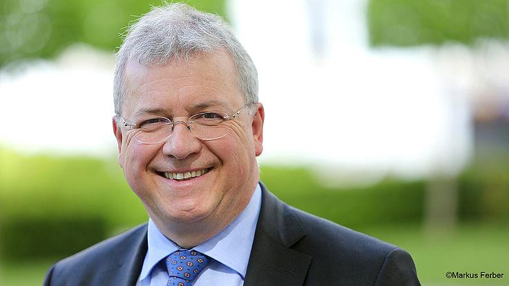 Ferber, ein freundlich blickender Mann mit randloser Brille, schütterem Haar aber Energie im Gesicht, lächelt freundlich.