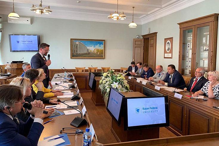 Konferenztisch mit Teilnehmern und die Aufmerksamkeit fesselnde Blumendeko in der Mitte