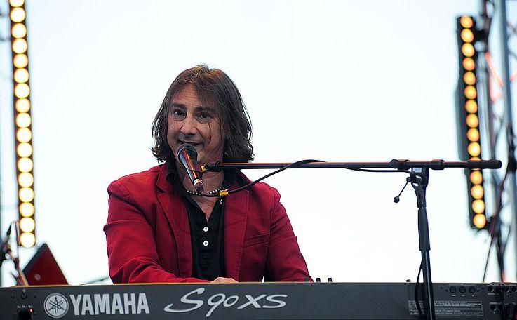 Fröhlicher Mann mit knalliger Jacke an einem Keyboard spielend und in ein Mikro singend.
