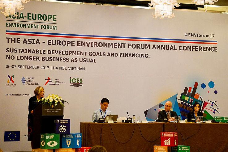 Ursula Männle steht an einem Podium, dahinter ist ein Transparent der Veranstaltung zu sehen.