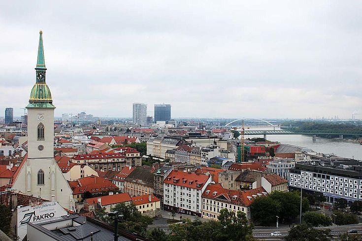 Blick auf Bratislava wohl von einem hohen Turm aus. Im Vordergrund ein spitz zulaufender Kirchturm. Rechts im Bild ein breiter Fluss, der von Brücken überspannt wird.