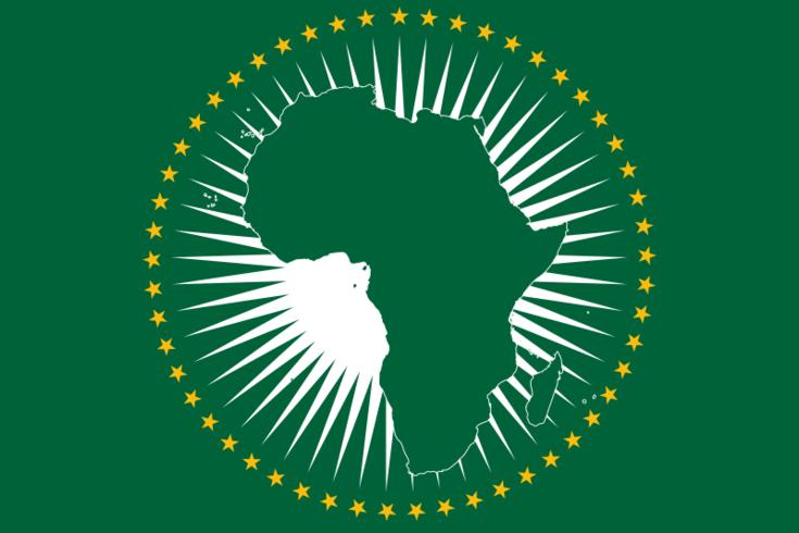 Dunkelgrüne Falgge mit dem Umriss von Afrika in einem Strahlenkranz und umgeben von goldenen Sternen