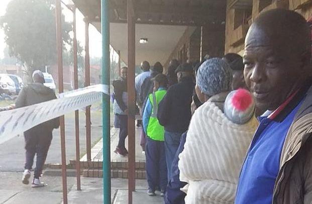eine Menschenschlange vor einem Wahllokal