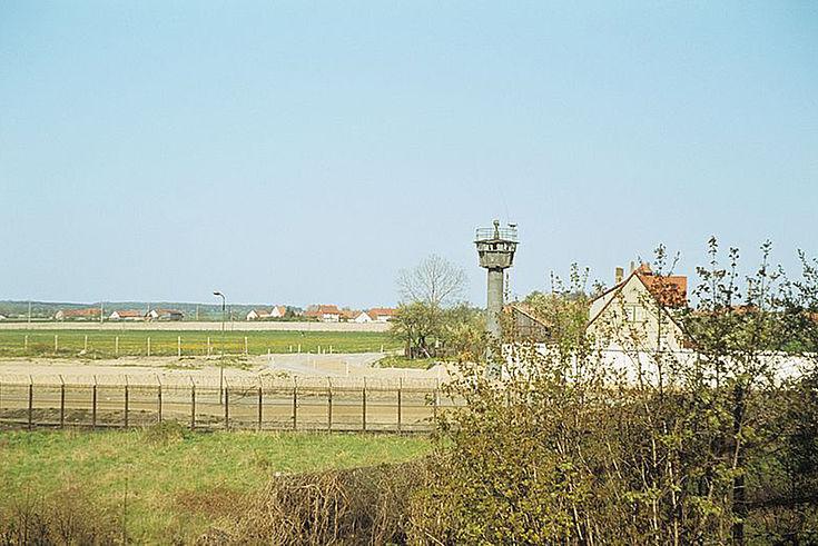 Blick auf die Grenze zwischen der BRD und der DDR. Hinter dem Grenzzaun erhebt sich ein Wachturm. Im Hintergrund ist ein Dorf zu sehen.