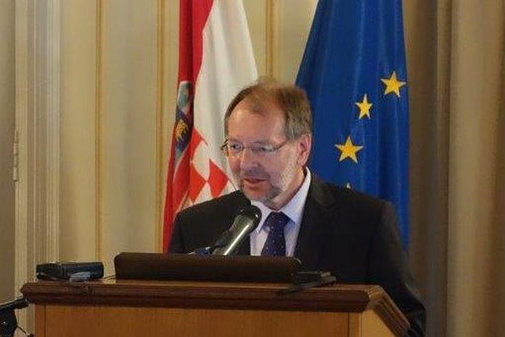 Peter Witterauf spricht an einem Rednerpult. Hinter ihm befinden sich die Flaggen von Europa und Kroatien