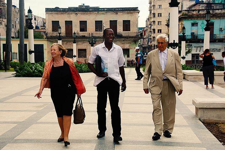 Ursula Männle und zwei Begleiter stemmen sich auf einem weiten Platz gegen den Wind.