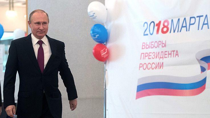 Putin schreitet forsch nach vorn. Daneben ein Wahlplakat.