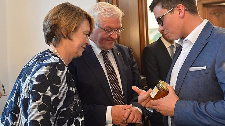 Ein junger Mann in schickem Anzug überreicht gerade dem interessierten Paar ein Glas Honig. Erklärt etwas.