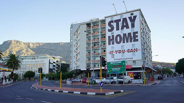 """Eine leere Straße vor einem Wohnhochhaus, an dessen Fassade ein riesiges Plakat hängt mit der Aufschrift: """"Stay home"""""""