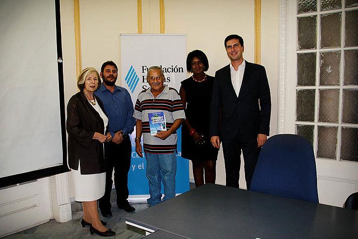 Ursula Männle links, lächelnder Kubaner mit Brochüre in der Hand mtitig und drei weitere Personen vor HSS-Stellwand.
