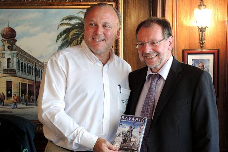 """Miguel Becker, Bürgermeister von Temuco, begrüßt Peter Witterauf zu einem Gesprächsaustauch. Der Bürgermeister zeigt eine DVA mit dem Titel """"Bavaria"""""""