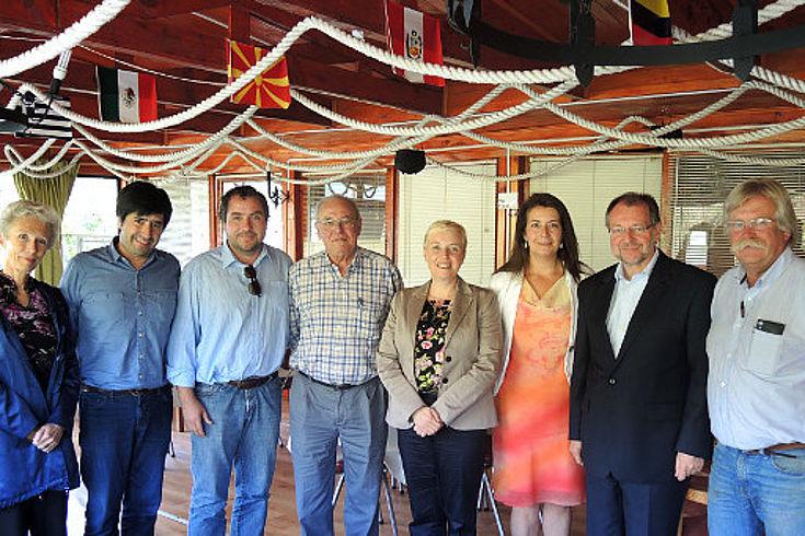 Dr Luther und Dr. Witterauf stehen mit einigen Mitgliedern des Projektpartners der HSS, Sirve a Chile, halbrund aufgestellt in einer Mehrzweckhalle