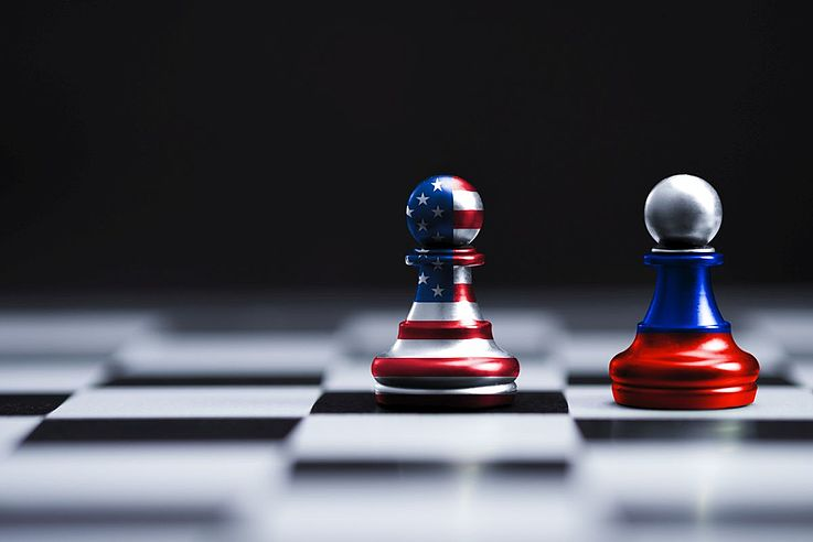 Zwei Schachfiguren, je in den Farben Russlands und der USA