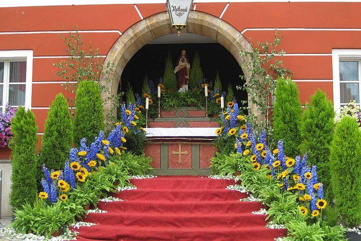 Auch vor dem Rathaus in Burglengenfeld ist ein Altar aufgebaut und festlich geschmückt. Wie bei den meisten Altären an Fronleichnam ist die Farbe rot zentrales Symbol für das Blut Christi.