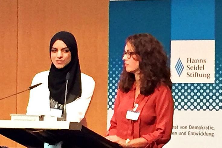 Zwei junge Frauen am HSS-Rednerpult. Links mit Kopftuch, rechts ohne.