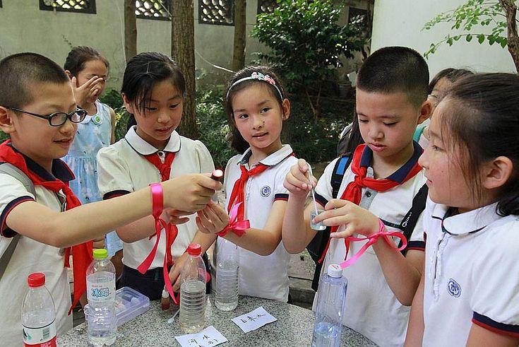 Fünf chinesische Schüler in weißen Hemden und Blusen mit roten Schals halten Röhrchen in den Händen mit Wasser und besprechen sich