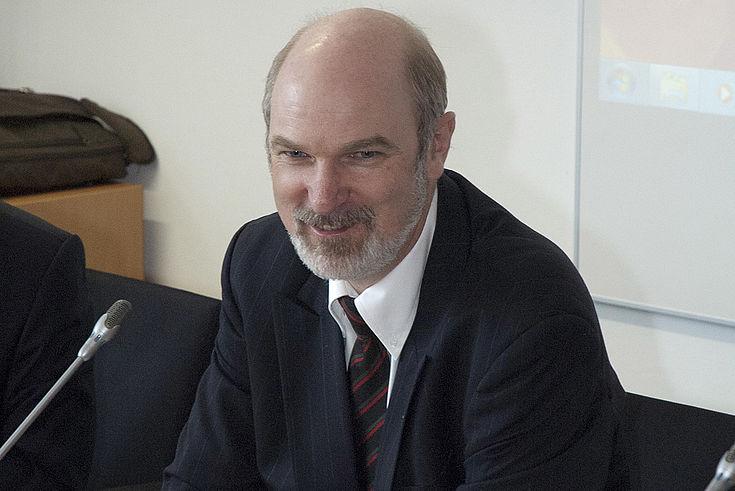 Älterer Mann mit Glatze sitzt in gutem Anzug vor einem Mikorfon und lächelt ein wenig hintergründig.