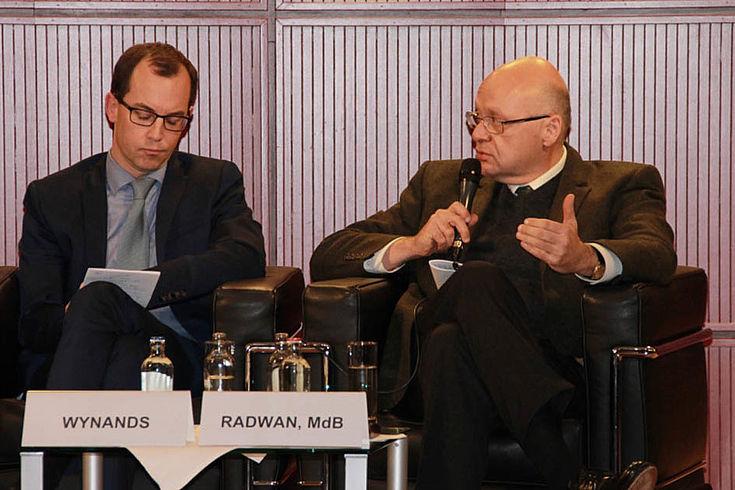 Die beiden Herren an ihrem Tisch auf dem Podium. Radwan (rechts) scheint gerade auf die Antwort von Herrn Wynands zu warten, der mit niedergeschlagenen Augen sehr konzentriert wirkt.
