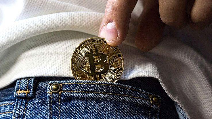Eine Münze wird von einer Person in dessen Hosentasche geschoben.
