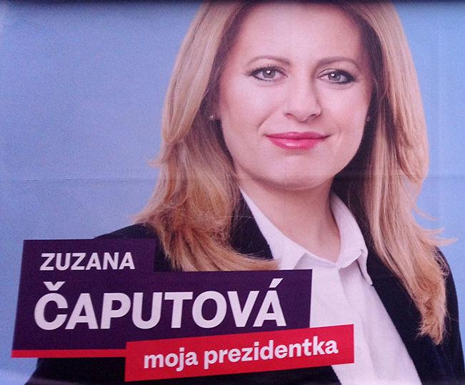Attraktive Frau mit ordentlicher Bluse, Blazer und offenen Haaren und entschlossenem Blick schaut von einem schlichten Wahlplakat.