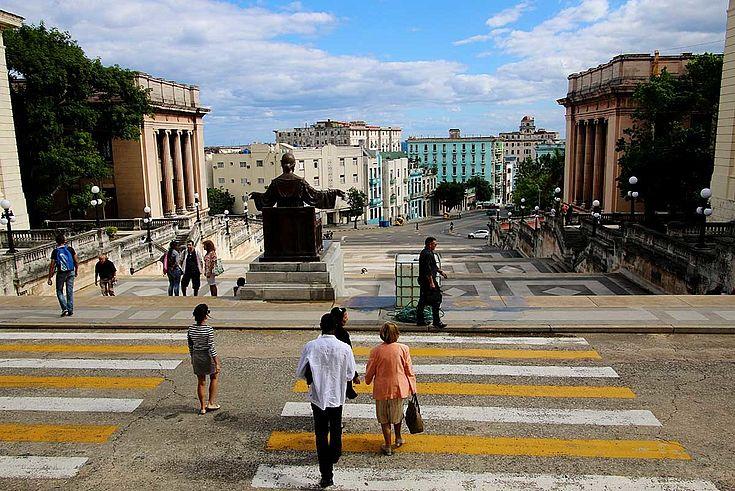 Weites Bullevard mit einer Messingstatue mittig. Rechts und links der Straße die altmodischen Häuser Havannas.