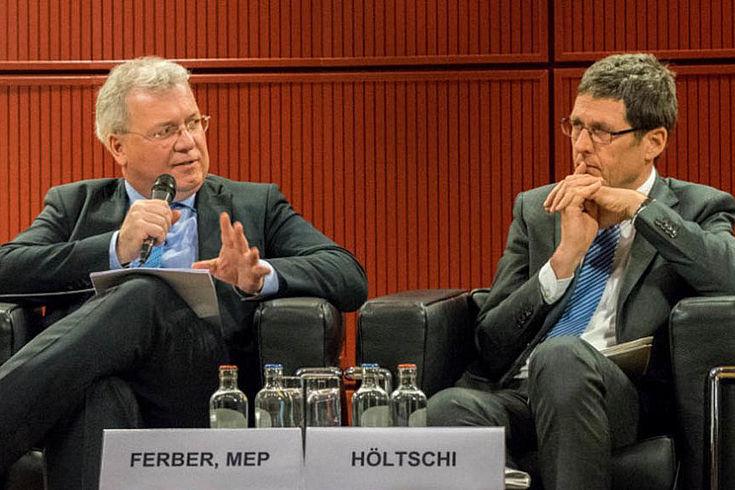 Zwei elegante Herren an einem Tischchen (offenbar ein Podium) im Gespräch. Der Linke erklärt gerade einen Punkt, der Rechte lauscht nachdenklich.