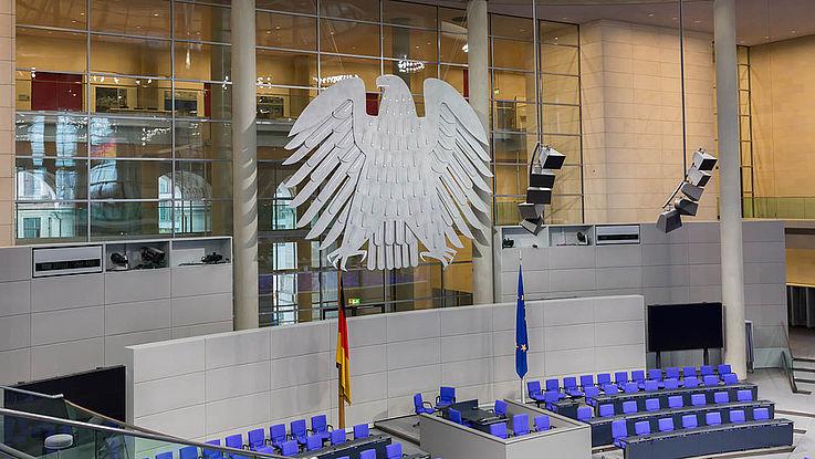 Bundestag Innenraum: Ein großer Saal mit einem riesen Adler über einem zentralen Rednerpult